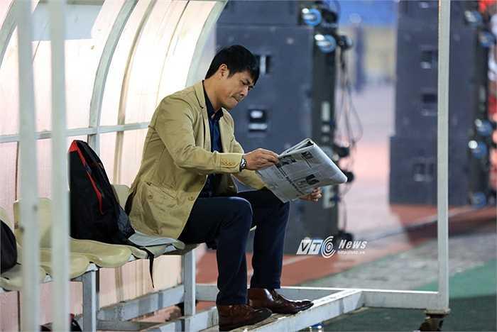 HLV Hữu Thắng bắt đầu trận đấu đầu tiên trên cương vị HLV trưởng ĐTVN bằng việc đọc báo. Bài báo ông đọc tối qua viết về chính màn ra mắt của mình và bữa tiệc bóng đá tri ân các cựu cầu thủ. (Ảnh: Phạm Thành)