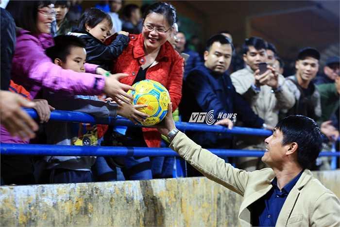 Hữu Thắng tặng quả bóng có chữ ký của các cầu thủ cho một bé trai trên khán đài Hàng Đẫy.(Ảnh: Phạm Thành)