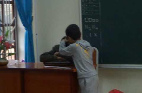 Hình ảnh thầy giáo nằm gục trên bàn để học sinh nhổ tóc bạc - Ảnh cắt từ clip