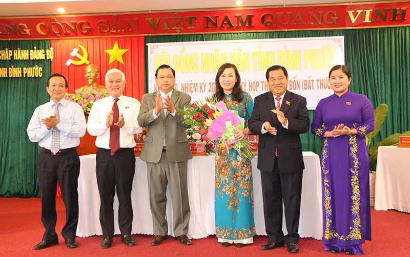 Bà Huỳnh Thị Hằng (thứ ba từ phải sang) nhận hoa chúc mừng của lãnh đạo Tỉnh ủy, HĐND, UBND, Uỷ ban MTTQ Việt Nam tỉnh.