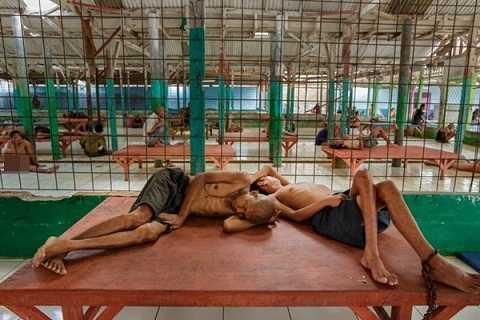Các bệnh nhân nam và nữ được ngăn cách với nhau bởi hàng rào làm bằng dây thép gai.