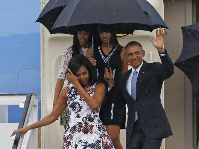 Tổng thống Obama cầm ô che cho vợ khi xuống sân bay - Ảnh: Reuters