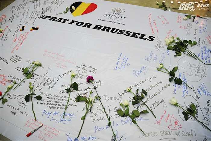Những dòng chữ chia buồn, hoa hồng trắng và dải ruy băng quốc kỳ Bỉ dành cho các nạn nhân