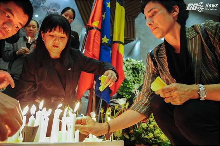 Phu nhân đại sứ Pháp, bà Eva Nguyễn Bình (phải) thắp nến tưởng niệm các nạn nhân