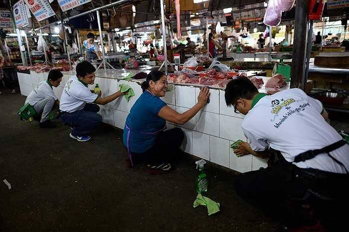 Ở một nơi khác, người phụ nữ bán hàng trong chợ Tân Chánh Hiệp (TP.HCM) vui mừng khi được lau chùi, dọn dẹp quầy hàng. Không khí của khu chợ trở nên náo nhiệt hơn nhờ các bạn trẻ mặc áo trắng xanh