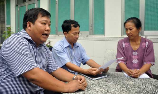 Ông Trần Quang Hiền (bìa trái) và ông Phạm Tấn Chiểu đến nhà để ghi nhận ý kiến của bà Đinh Thị Thu Hồ chiều 12-10 - Ảnh: ĐÔNG HÀ