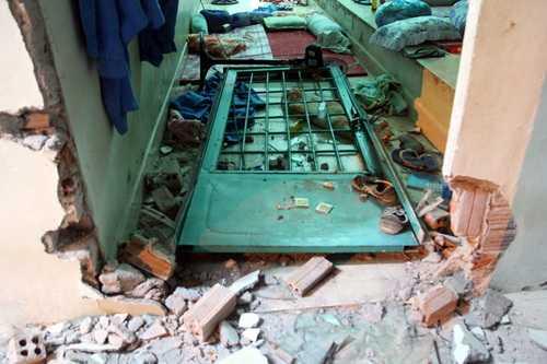 Một cánh cửa bị đập vỡ, xô đạp vào trong phòng.