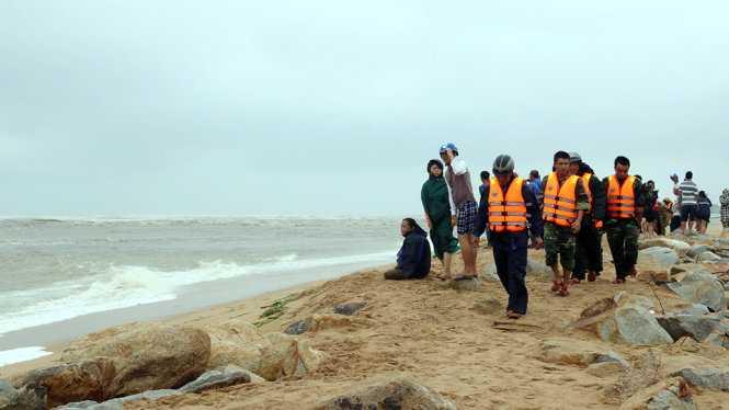Người nhà bốn ngư dân ở TP Tuy Hòa và các lực lượng chức năng bất lực vì không cứu được các nạn nhân do sóng biển quá lớn - Ảnh: NGÔ XUÂN