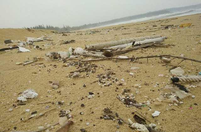 Dầu vón cục lẫn trong rác dạt vào bờ biển