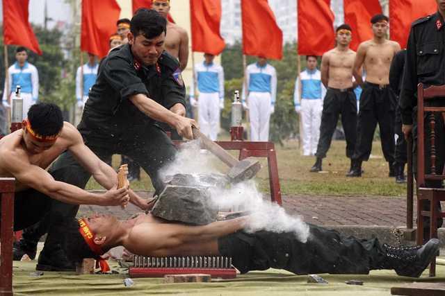 Sức chịu đựng phi thường của một chiến sỹ khi thực hiện bài tập nằm trên đinh, đặt đá lên ngực, sau đó dùng búa tạ đập vỡ phiến đá.