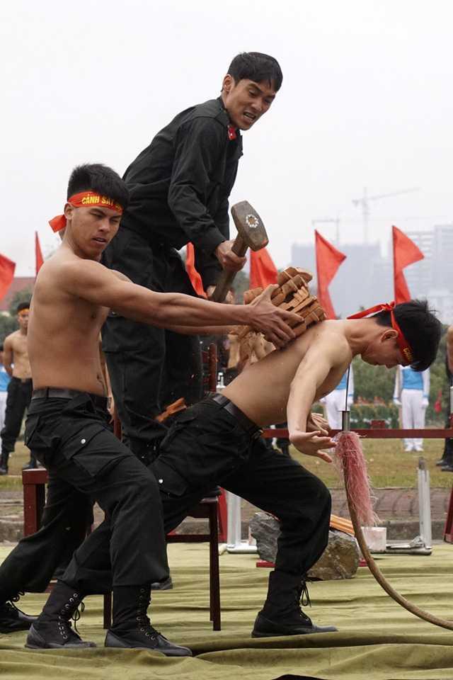 Khả năng khí công phi thường của một chiến sỹ trong bài trình diễn đè lưỡi giáo nhọn vào cổ đồng thời dùng búa tạ đập vỡ gạch đặt trên lưng.