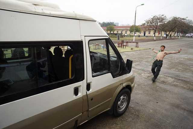Một chiến sỹ dùng răng kéo chiếc xe ô tô chở khách.