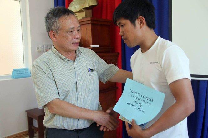 Ông Trương Ngọc Minh (trái) trao tiền ủng hộ một gia đình của thủy thủ tàu Hải Thành 26 - Ảnh: ĐÔNG HÀ