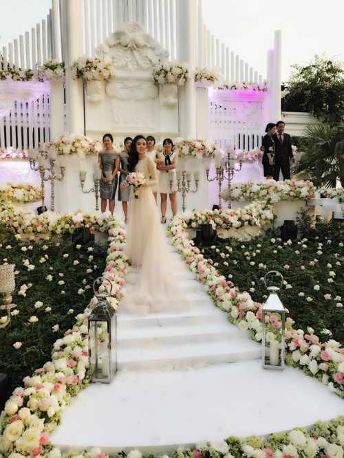 Lễ cưới được tổ chức ngoài trời. Không gian trang trí ấn tượngvới hai tông màu trắng - hồng chủ đạo.