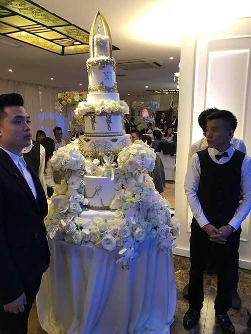 Bánh cưới 7 tầng cao gần 2m tông trắng đính ngập hoa tươi.