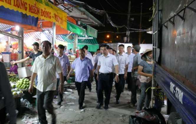Gần 5 giờ sáng, Thủ tướng xuống xe, ông rảo bước vào khu trung tâm chợ đầu mối rau quả lớn nhất khu vực nội thành Hà Nội, nhiều người dân bất ngờ về sự hiện diện của người đứng đầu Chính phủ - Ảnh: LÊ KIÊN