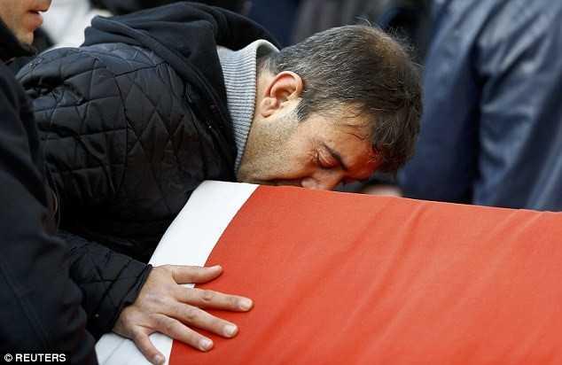 Người đàn ông hôn quan tài chứa thi thể của Ayhan Arik, một trong số những người thiệt mạng. Cảnh sát vẫn chưa bắt được kẻ xả súng. Ảnh: Reuters.
