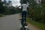Nam thanh niên đứng thả 2 tay trên xe máy chạy tốc độ cao
