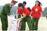 Chiến sỹ công an trẻ mặc áo cờ đỏ sao vàng làm sạch môi trường biển