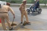 Xe khách tràn dầu trên quốc lộ, CSGT đội nắng xúc cát rải đường