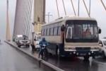Xe khách biển xanh chắn gió cho xe máy qua cầu Bãi Cháy trong mưa bão