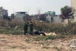 Thi thể người đàn ông bên xe máy trong bãi đất trống