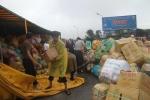 Xe container chở dừa lật giữa đường, dân đội mưa gom giúp tài xế