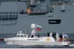 Chiếc thuyền chở tổng thống Nga đi qua một chiến hạm. (Ảnh: RIA Novosti)