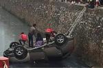 Dân cạy cửa cứu tài xế trong chiếc ô tô 'phơi bụng' dưới kênh nước