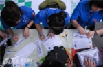 Sinh viên tình nguyên giúp thí sinh đăng ký gửi đồ  - Ảnh: Tùng Đinh