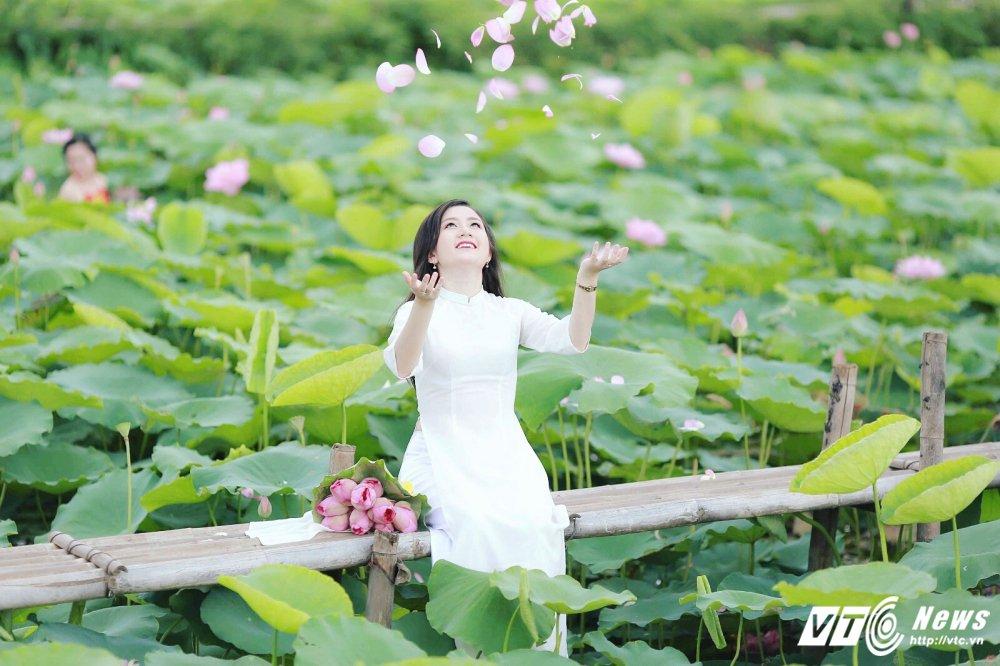 Hot girl DH Kiem sat e ap trong ta ao dai do sac ben nhung doa sen hong hinh anh 3