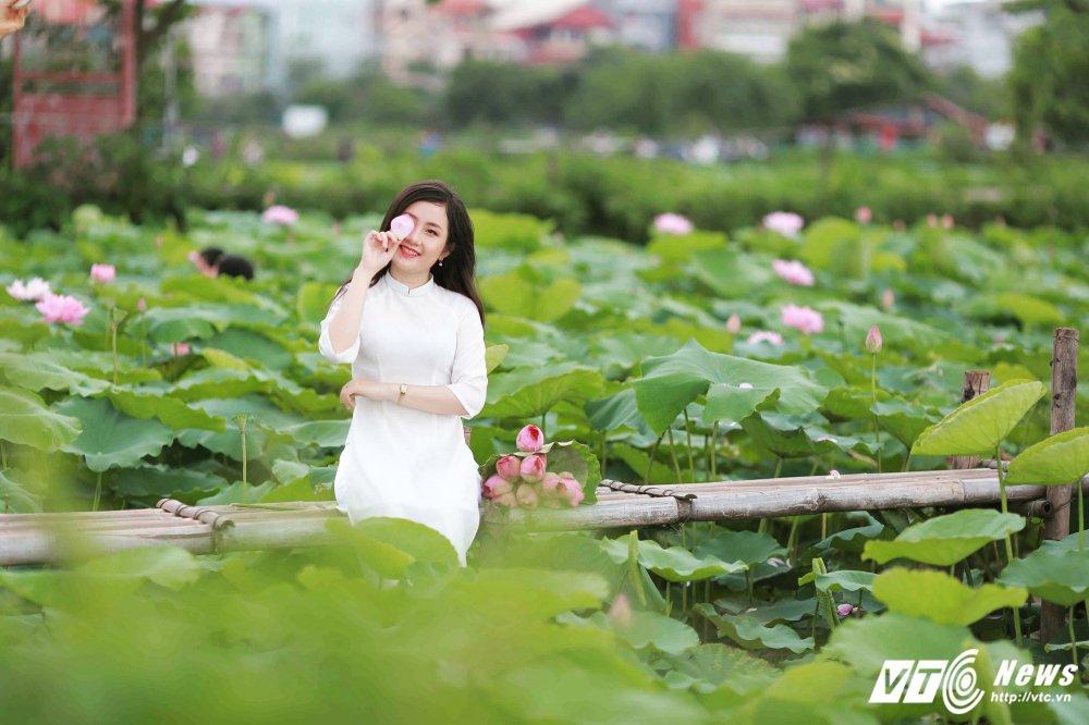 Hot girl DH Kiem sat e ap trong ta ao dai do sac ben nhung doa sen hong hinh anh 5
