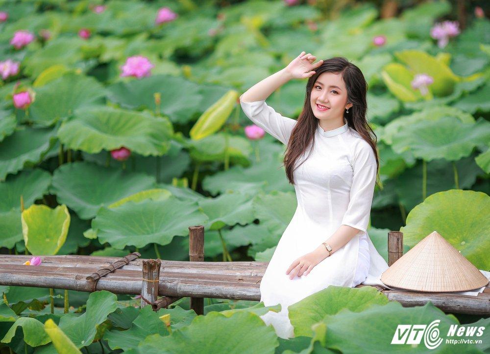 Hot girl DH Kiem sat e ap trong ta ao dai do sac ben nhung doa sen hong hinh anh 1