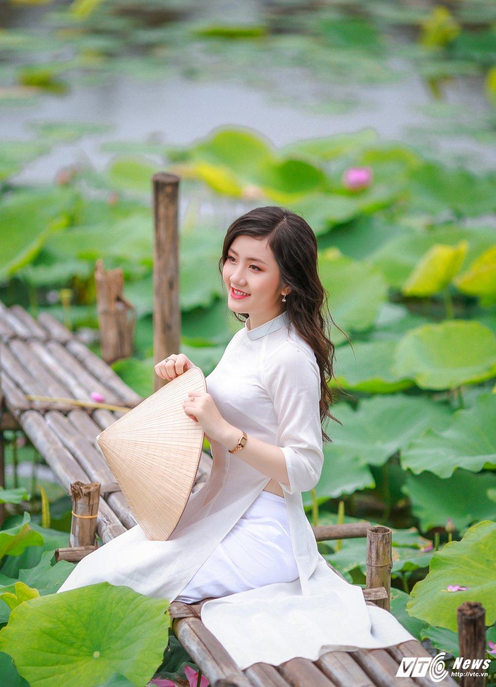 Hot girl DH Kiem sat e ap trong ta ao dai do sac ben nhung doa sen hong hinh anh 8