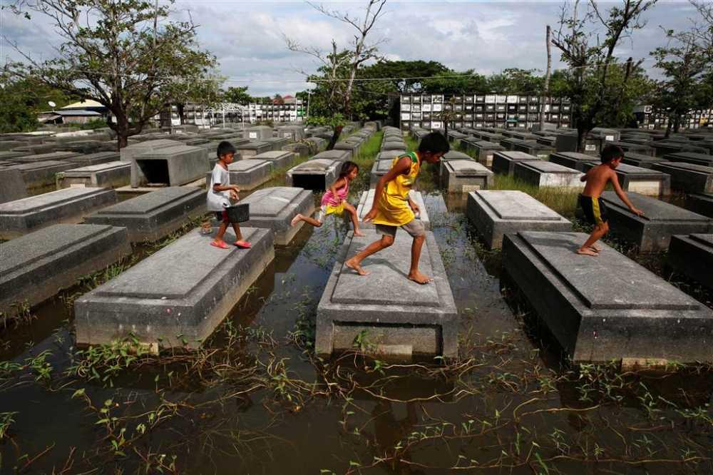 Anh an tuong trong tuan: Tre em Philippines nhay tren nhung ngoi mo bi ngap lut hinh anh 1