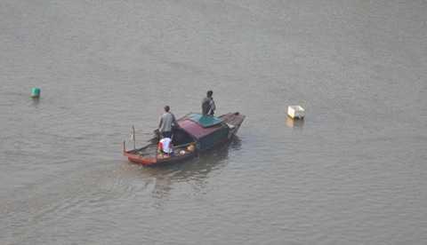 Gia đình thuê thuyền tìm kiếm xác chị Huyền trên sông Hồng.