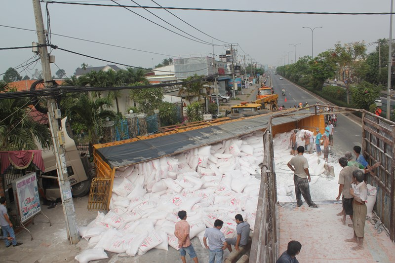 Chiếc xe container chở bột mì lật ngang trên quốc lộ, hàng chục bao mì tràn xuống đường