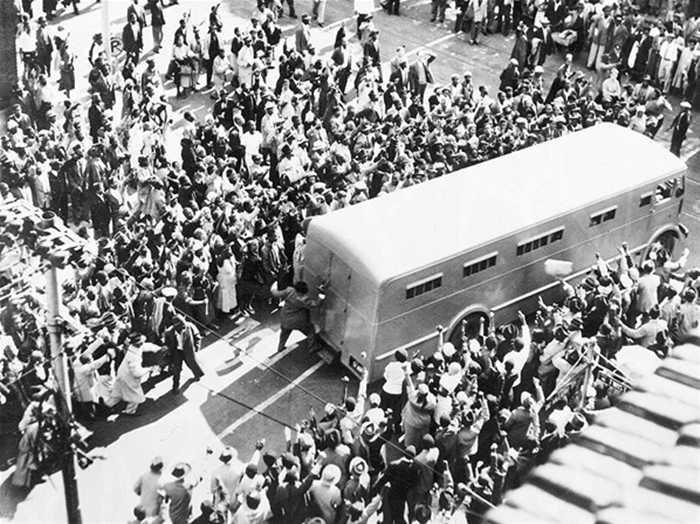 Đám đông vây quanh xe cảnh sát chở ông Nelson đến tòa án để luận tội 'phản quốc' năm 1956