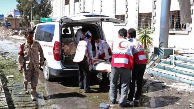 Nhân viên y tế đưa một nạn nhân lên xe cấp cứu sau vụ nổ trong khuôn viên Bộ Quốc phòng Yemen