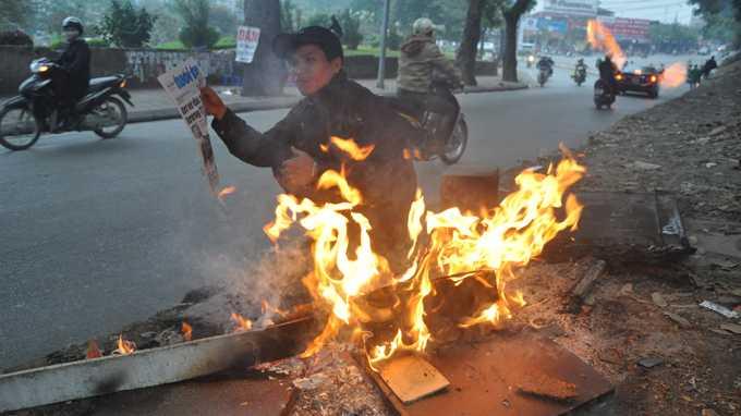 Người lao động vừa đọc báo vừa sưởi ấm ngay bên vệ đường thủ đô - Ảnh: Quang Thế (TTO)