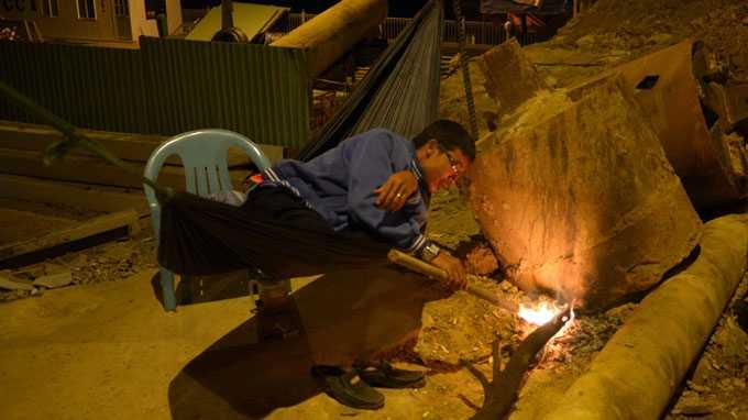 Người dân đốt lửa sưởi ấm trong lúc trực đêm tại công trường xây dựng cầu Bông, Q.Bình Thạnh, TP.HCM. Ảnh: Khoa Định - TTO