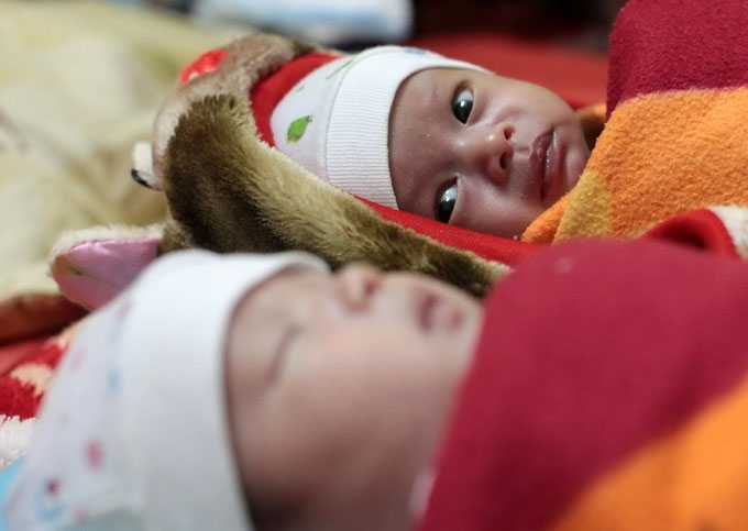 Một cái ngáp đáng yêu của bé Hồ Sỹ Hoàng Đức (trên), và ánh mắt liếc nhìn anh của bé Hồ Sỹ Hoàng Hải - Ảnh: Nguyễn Khánh