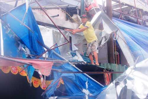 Người dân mạo hiểm chống đỡ lại nhà trong mưa bão. Ảnh: TNO
