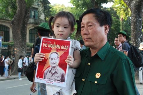 Một cháu nhỏ cùng ông mang theo hình Đại tướng Võ Nguyên Giáp đến viếng tại căn nhà số 30 Hoàng Diệu, Hà Nội. Ảnh: Nguyễn Dũng