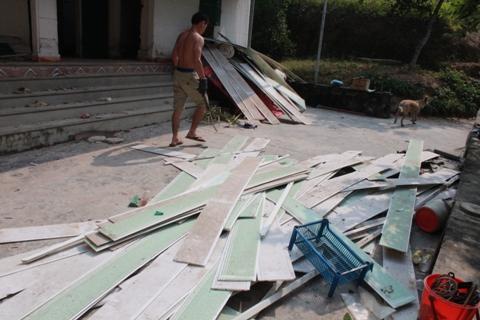 Gia đình anh Hưng thu dọn đồ đạc từ đống đổ nát.