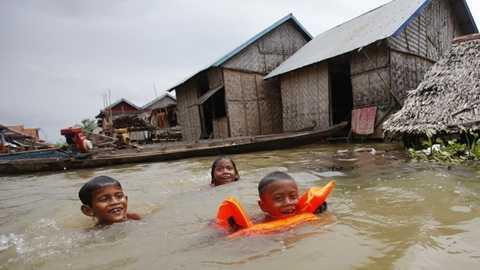 Trẻ em bơi lội và còn tỏ ra thích thú trước nhà khi mực nước dâng cao vào ngày 7/10 ở tỉnh Kandal - Ảnh: Reuters