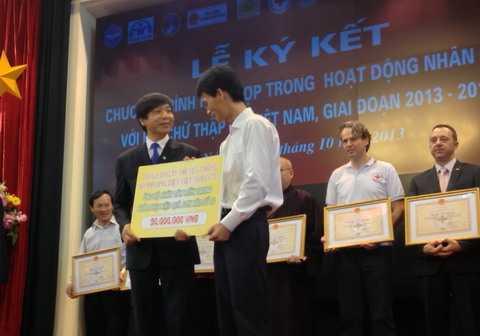 Ông Đoàn Văn Thái, Phó chủ tịch, Tổng thư ký Trung Ương hội Chữ thập đỏ Việt Nam nhận tiền quyên góp từ Tổng giám đốc VTC Nguyễn Xuân Cường (phải) (Ảnh: Hà Thanh)