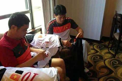 HLV phó Phạm Như Thuần cùng Trưởng đoàn Dương Nghiệp Khôi khâu băng tang cho đội U19 Việt Nam