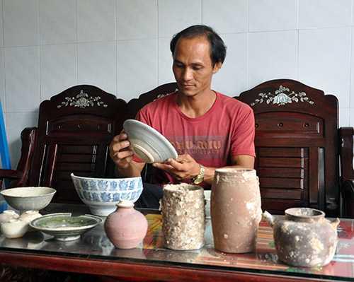 Anh Đinh Tấn Tàu mân mê những món cổ vật đang cất giữ tạinhà. Ảnh: Báo Quảng Nam