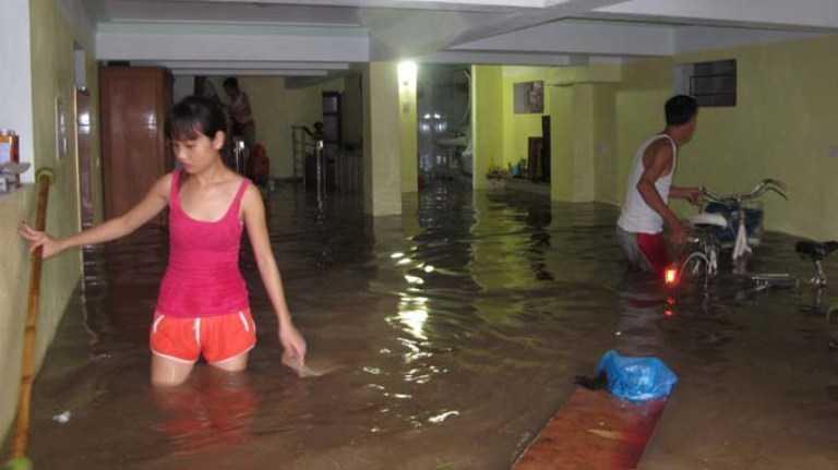 Nước dâng nhanh khiến nhiều người dân không kịp di chuyển đồ đạc. (Ảnh: Tuổi trẻ)